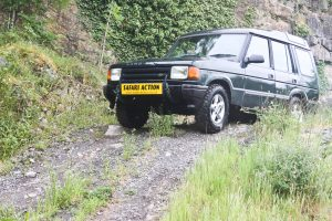Land rover driving over a small hill