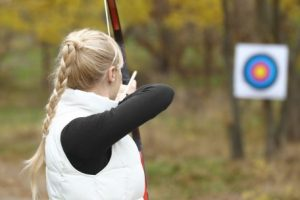 Girl shooting an arrow at a target, archery