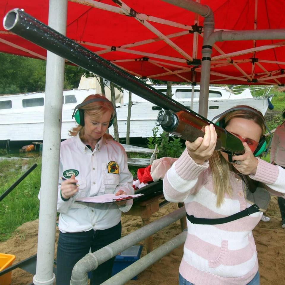 Girl shooting a shotgun clay pigeon